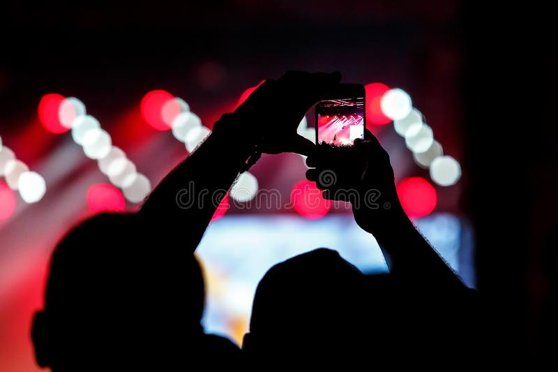 Record on a mobile phone of a concert, show. Holds a smartphone in hands royalty free stock photo