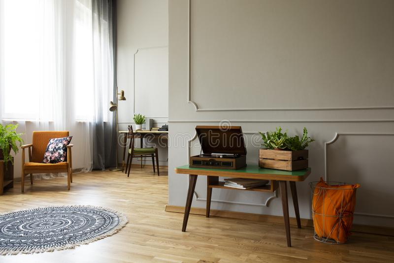 Record player and plant on table in vintage living room interior with rug and armchair. Real photo. Concept royalty free stock photos