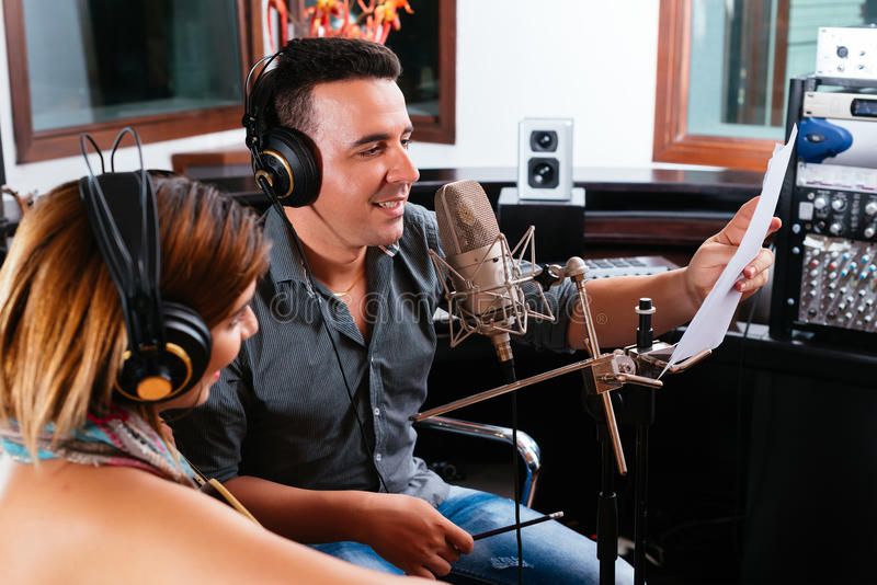 Record producer. Showing young singer the right way to perform the song stock photography