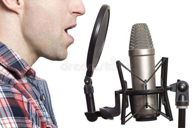 Record voice to microphone in studio. young man sings in studio condenser microphone with spider isolated on white background. Write song in sound recording royalty free stock photo