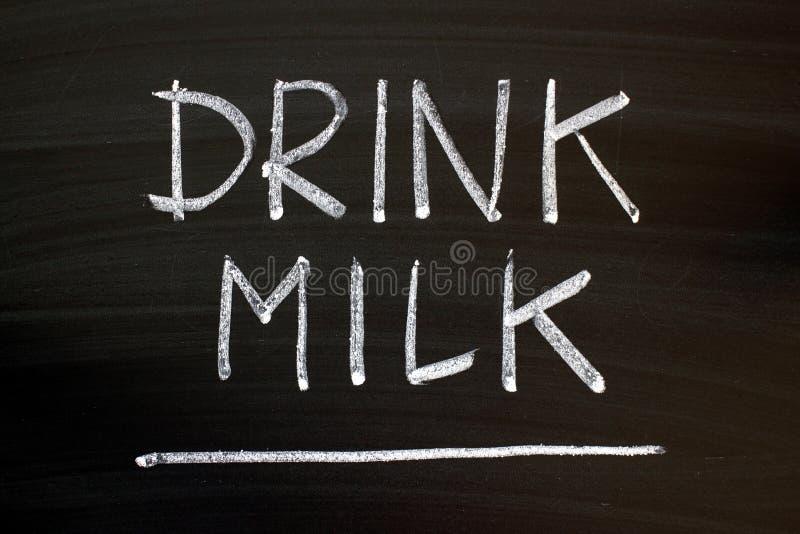 Recordatorio de la leche de la bebida escrito en una pizarra imagenes de archivo