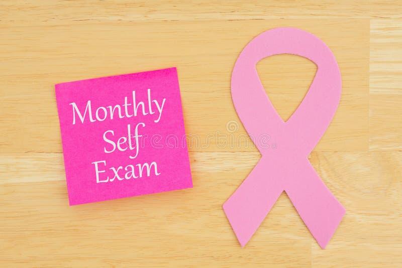 Recordatorio mensual del examen del uno mismo con la cinta rosada del cáncer imagenes de archivo
