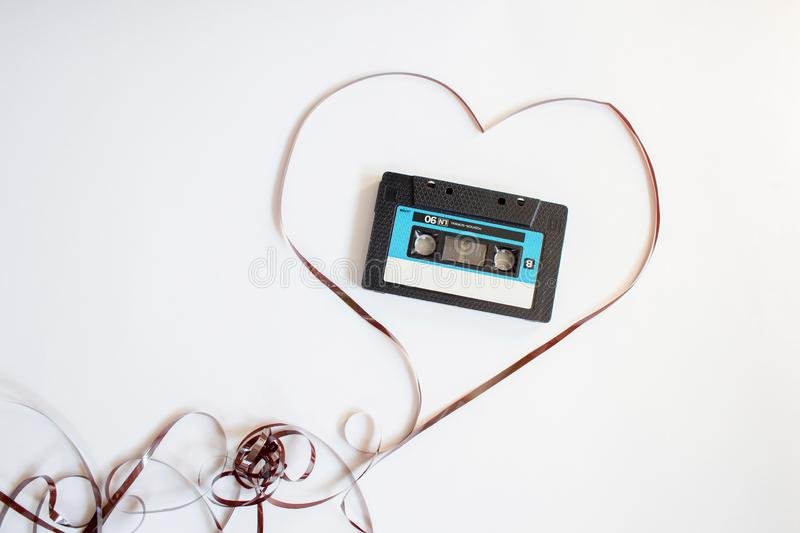 The recorder cartridge from the 90th lies in heart from a magnetic tape. On a white background royalty free stock photography