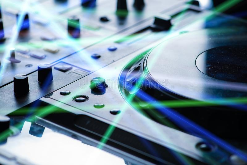 Recording mixer in the rays of light. DJ booth at a nightclub stock image
