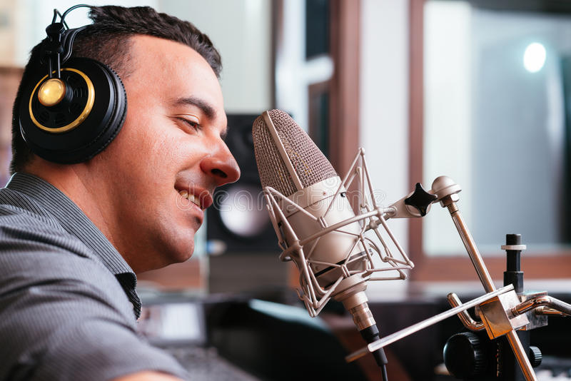 Recording a song. Man recording a song in the studio, side view stock photography
