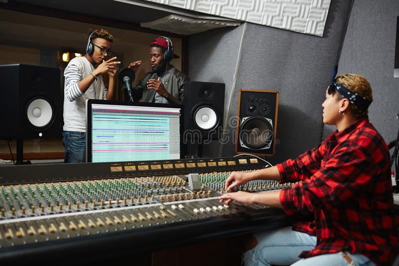 Recording songs. Two young singers performing their songs in record studio with help of operator stock image