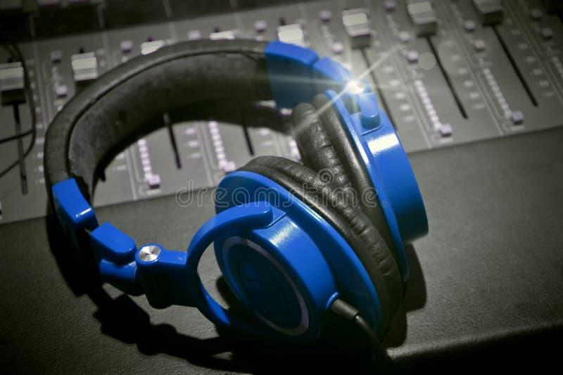 Recording studio headphones black white and blue. Music recording studio table close up black and white music photography headphones professional equipment stock photography