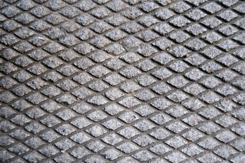 Recorte da grade do cimento no asfalto imagens de stock royalty free