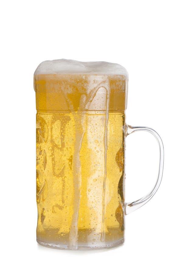 Recorte de la taza de cristal alta que desborda con la cerveza imagen de archivo libre de regalías