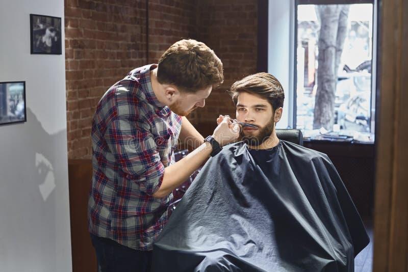 Recorte de un bigote en la peluquería de caballeros imagenes de archivo