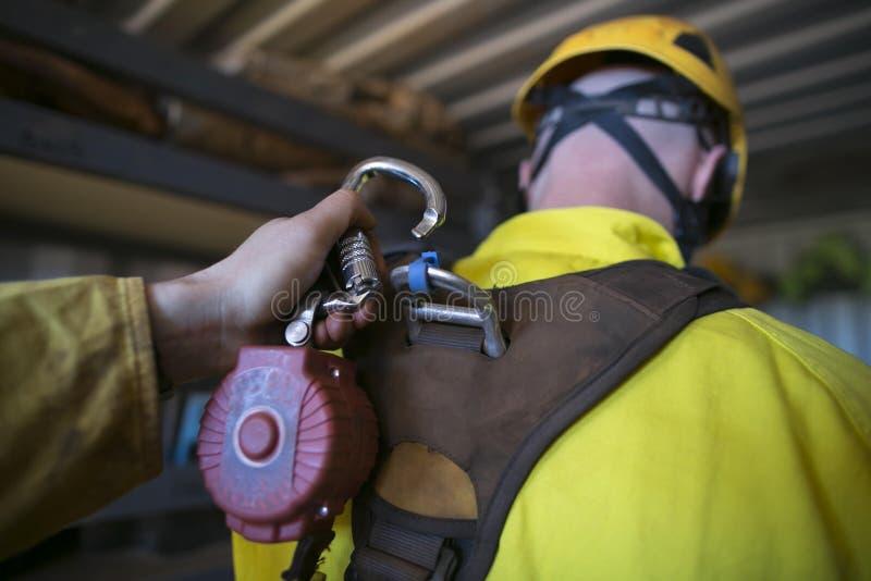 Recortes masculino de la mano que cierra el mosquetón que conecta con el uno mismo que contrae el dispositivo de seguridad del am imágenes de archivo libres de regalías