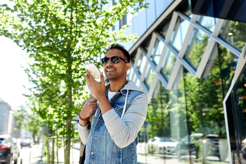 Recorving stämmameddelande för man på smartphonen i stad royaltyfri fotografi