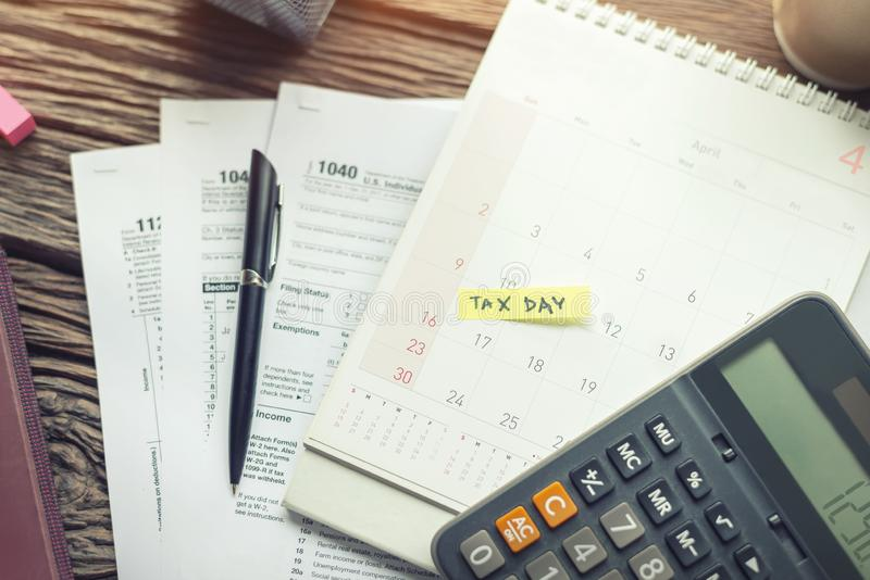 Recouvrement des dettes et jour d'impôts avec la note de rappel de calendrier de date-butoir, U S feuille d'impôt 1040, calculatr image libre de droits