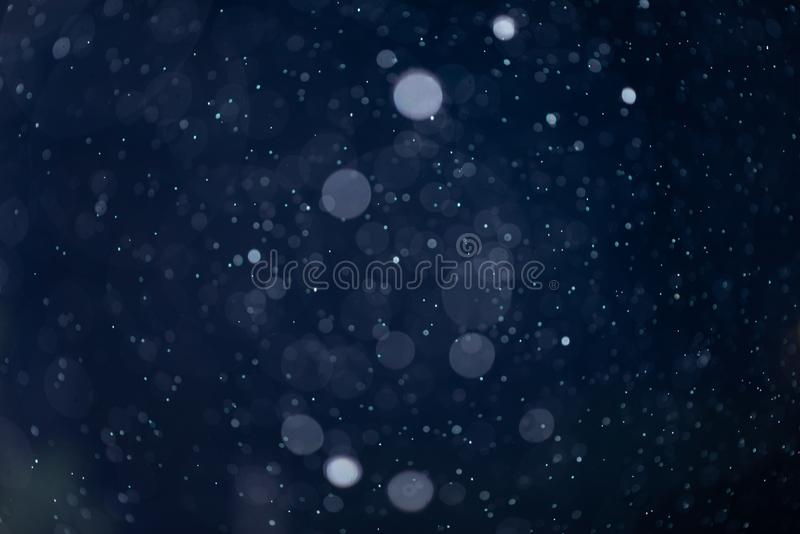 Recouvrement en baisse de texture de bokeh de neige ou de pluie sur le fond bleu photo libre de droits