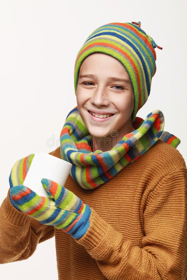 The recovering boy holds a cup of tea, medicine, got sick. In a sweater, a cap, gloves, a disease, cold, flu, winter, fall. On a white background in studio stock photos