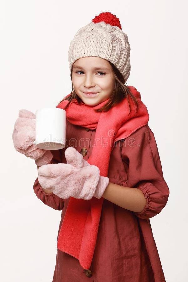 The recovering girl holds a cup of tea, medicine, ached. In a jacket, a cap, gloves, a disease, cold, flu, winter, fall. On a white background in studio stock photography