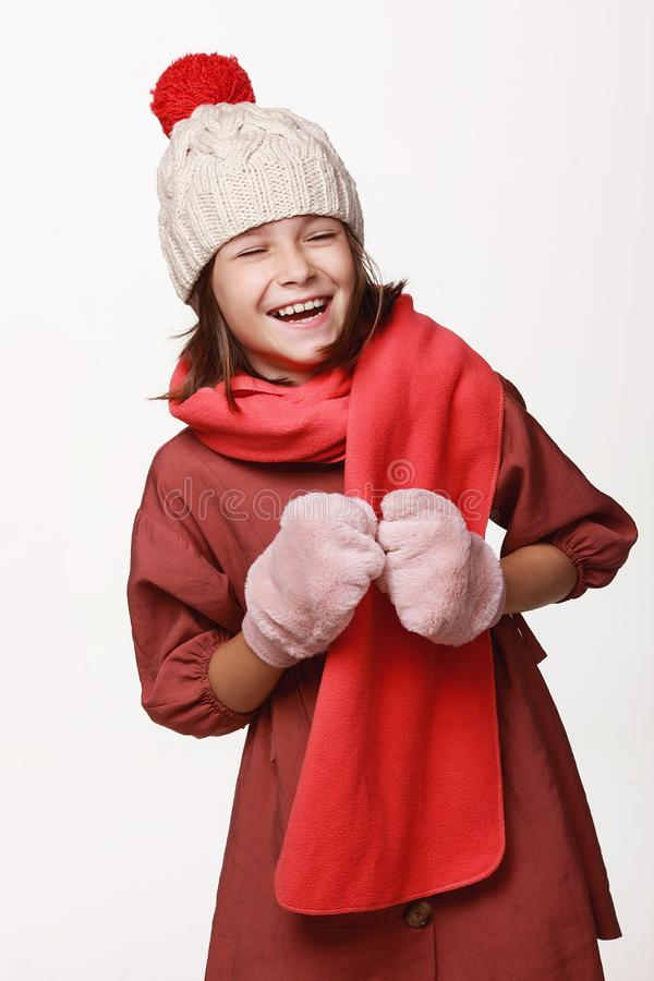 The recovering laughing girl in a jacket, a cap, gloves, a disease, cold, flu, winter, fall. Immunity. On a white background in studio royalty free stock images