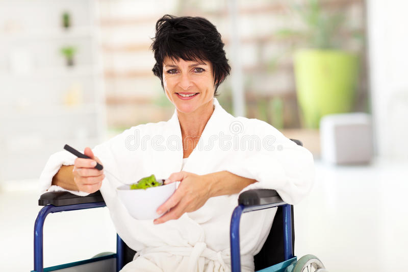 Recovering middle aged woman. Eating salad on wheelchair royalty free stock image