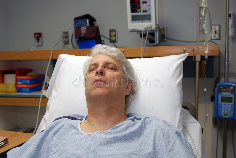 Recovery. Gray haired man in hospital bed recovering from surgery
