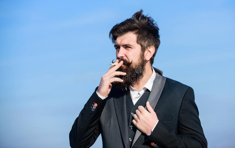 Recovery from nicotine addiction must involve changing our relationship to smoking. Man beard and mustache hold. Cigarette. Bearded hipster smoking cigarette stock photo