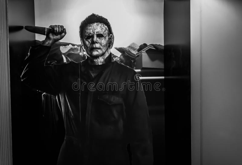 Recreação de uma cena do filme 1978 Dia das Bruxas; Michael Myers a forma que guarda exposições de uma faca no teatro fotografia de stock royalty free