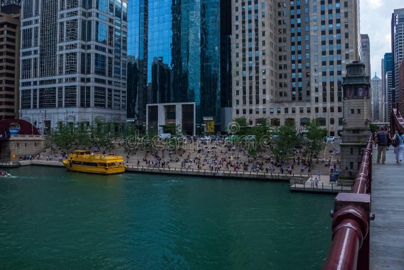 Recreação de Chicago River com táxi da água, executivos que almoçam em escadas do riverwalk, pares que andam na ponte fotos de stock