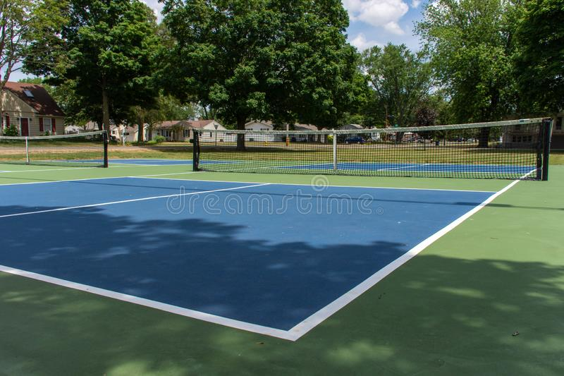 Recreatieve sport van pickleballhof in Michigan, de V.S. die een leeg blauw en groen nieuw hof bij een openluchtpark bekijken Gro stock foto's
