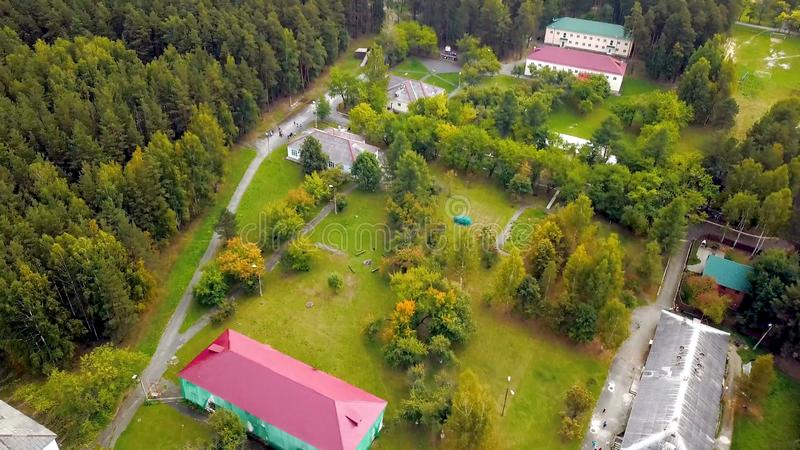 Recreation center in forest near lake. Stock footage. Top view of beautiful tourist base in picturesque area with lake. Rest at camp site surrounded by nature royalty free stock image