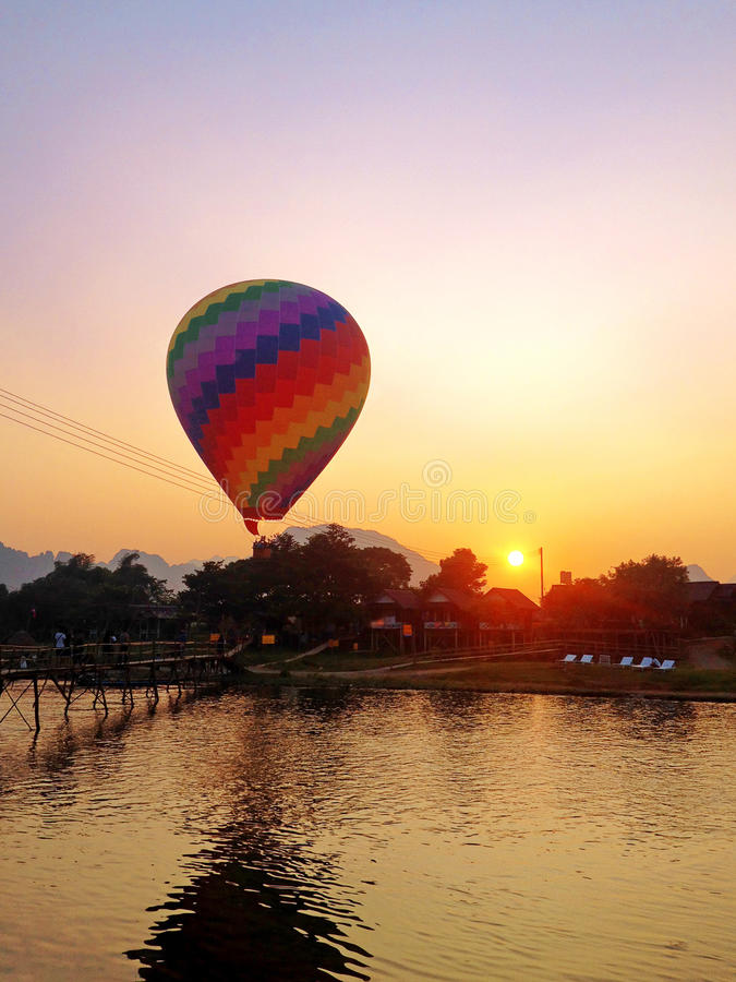 Recreation. Hot air balloon flying over the river royalty free stock image