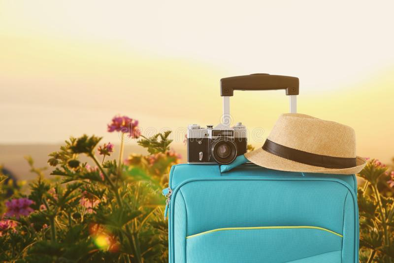 Recreation image of traveler luggage, camera and fedora hat infront of a rural lanscape. holiday and vacation concept.  stock photos