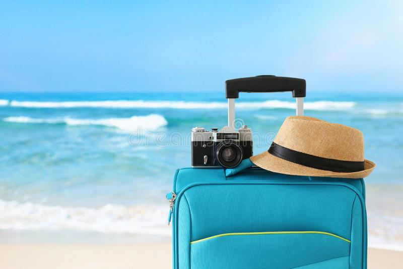 Recreation image of traveler luggage, camera and fedora hat infront of tropical background. holiday and vacation concept stock photography