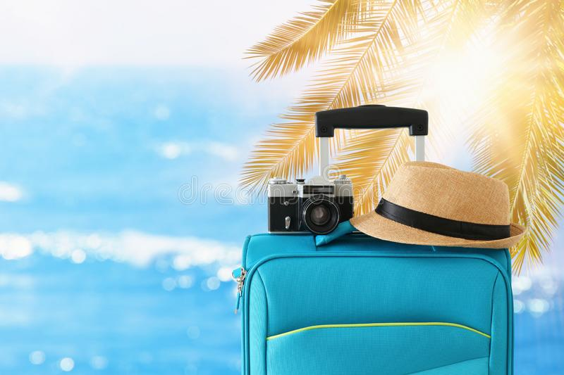 Recreation image of traveler luggage, camera and fedora hat infront of tropical background. holiday and vacation concept stock photos