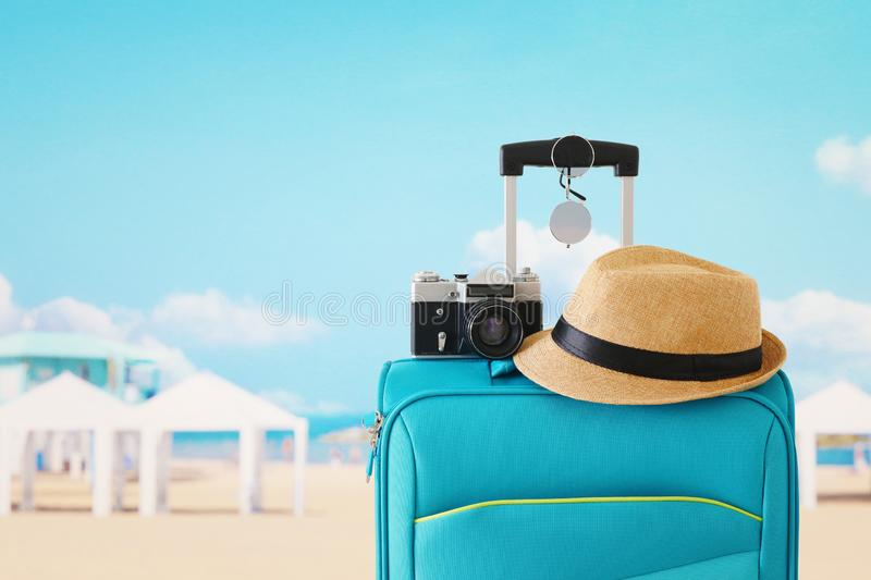 Recreation image of traveler luggage, camera and fedora hat infront of tropical background. holiday and vacation concept royalty free stock photography