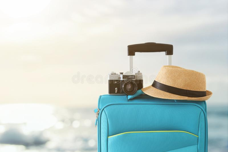 Recreation image of traveler luggage, camera and fedora hat infront of tropical sunset background. holiday and vacation concept royalty free stock image