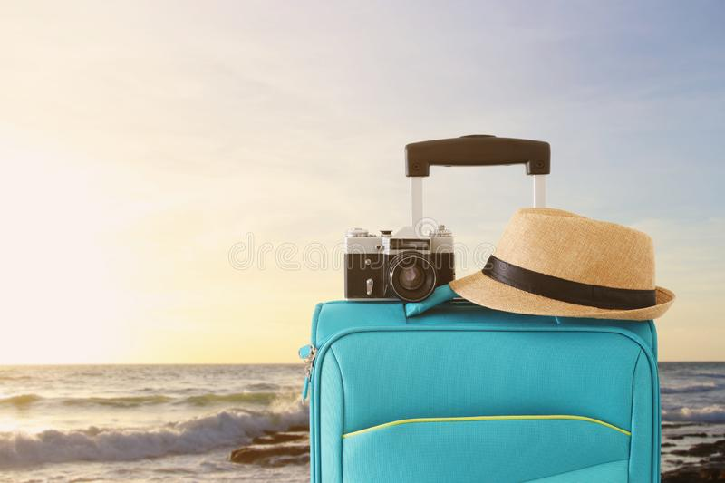 Recreation image of traveler luggage, camera and fedora hat infront of tropical sunset background. holiday and vacation concept royalty free stock photography
