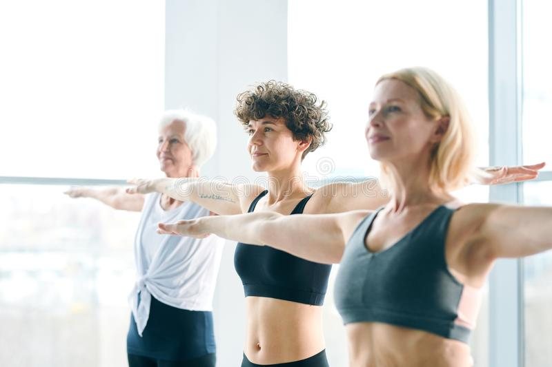 Recreation. Row of three active women outstretching their arms while exercising in contemporary fitness center at leisure stock photos