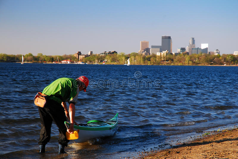 Recreation in an Urban setting. Kayaker prepares to enter Lake Calhoun, Minneapolis, Minnesota royalty free stock image