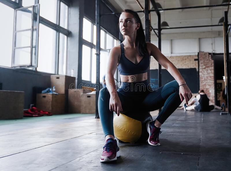 Motivated female workout fitness club, sit gym smile camera, wipe sweat off forehead, lean medicine ball crossfit. Recreation, wellbeing and sport concept royalty free stock photography