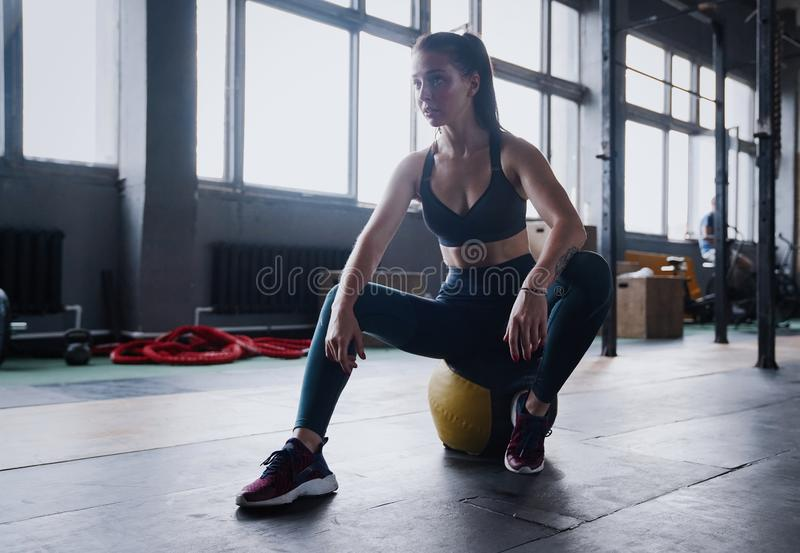 Motivated female workout fitness club, sit gym smile camera, wipe sweat off forehead, lean medicine ball crossfit. Recreation, wellbeing and sport concept stock images