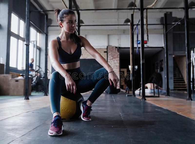 Motivated female workout fitness club, sit gym smile camera, wipe sweat off forehead, lean medicine ball crossfit. Recreation, wellbeing and sport concept royalty free stock images