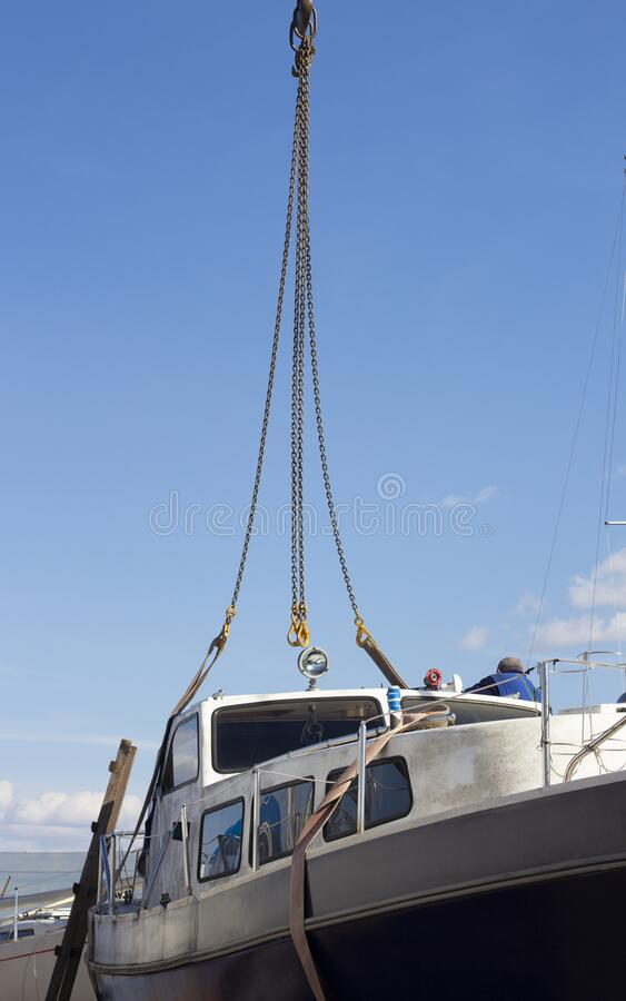 The boat being lifted by heavy industrial crane machinery against blue sky background. Recreational boat being lifted by heavy industrial crane machinery against royalty free stock images