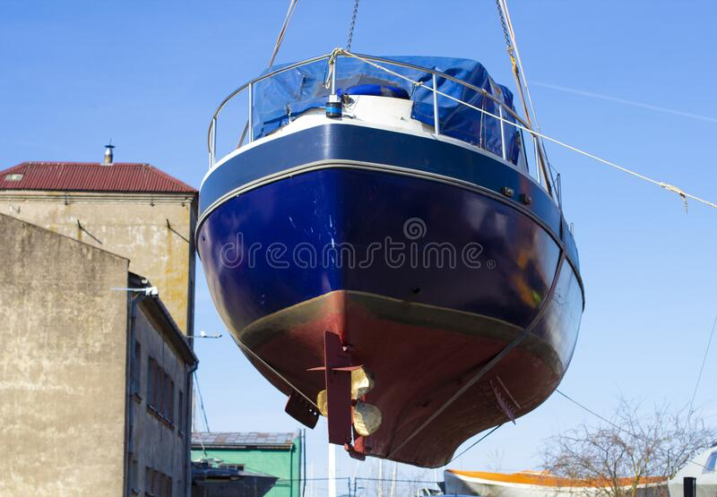 Recreational boat being lifted by heavy industrial crane machinery against blue sky background. The recreational boat being lifted by heavy industrial crane royalty free stock photos