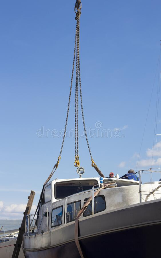 Recreational boat being lifted by heavy industrial crane machinery against blue sky background. The Recreational boat being lifted by heavy industrial crane royalty free stock image