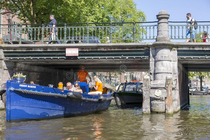 Recreational boats with tourists swim under the bridge in Amsterdam. Amsterdam, Netherlands - July 02, 2018: Recreational boats with tourists swim under the royalty free stock images