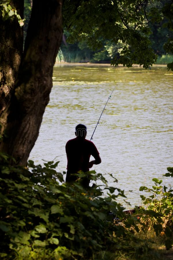 Recreational fisherman figure enjoys competition fishing, reeling the line on his rod, little forest lake, calm waves on water sur stock photo