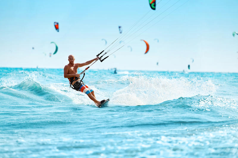 Recreational Sports. Man Kiteboarding In Sea Water. Extreme Sport Action stock images