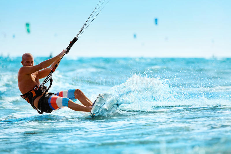 Recreational Sports. Man Kiteboarding In Sea Water. Extreme Sport Action royalty free stock images