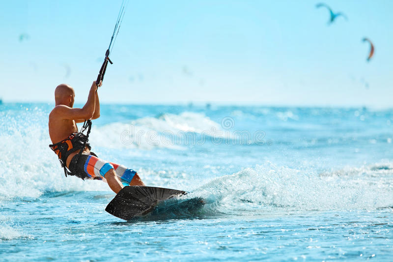 Recreational Sports. Man Kiteboarding In Sea Water. Extreme Sport Action stock photography
