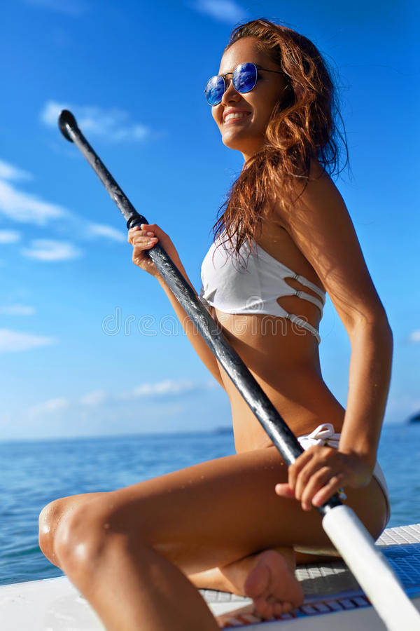 Recreational Sports. Woman Stand Up Paddle Boarding ( Surfing ). Recreational Sports. Healthy Happy Fit Woman With Body In Bikini sitting on Paddle Boarding ( stock photography