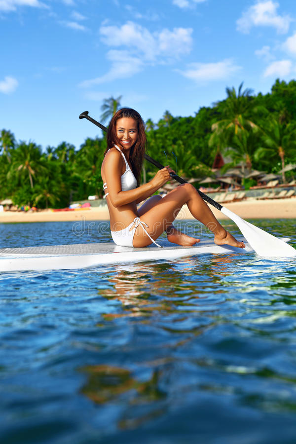 Recreational Sports. Woman Stand Up Paddle Boarding ( Surfing ). Recreational Sports. Healthy Happy Fit Woman With Body In Bikini Stand Up Paddle Boarding ( SUP stock photography